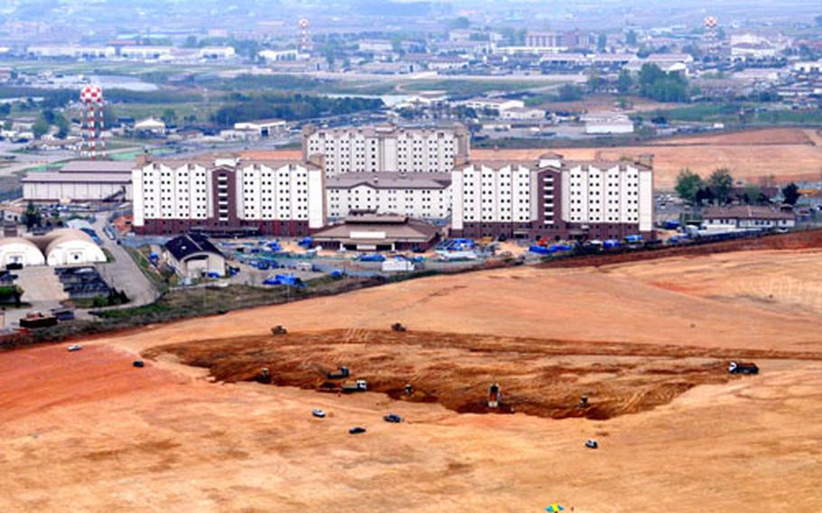 An aerial photograph taken Tuesday shows Camp Humphreys in South Korea and part of the new land onto which the post will expand by 2012. The first construction on the Parcel 1 of the new lands, seen in foreground, is to start in early June. In the background are new eight-story barracks and a dining hall in the post's MP Hill area.
