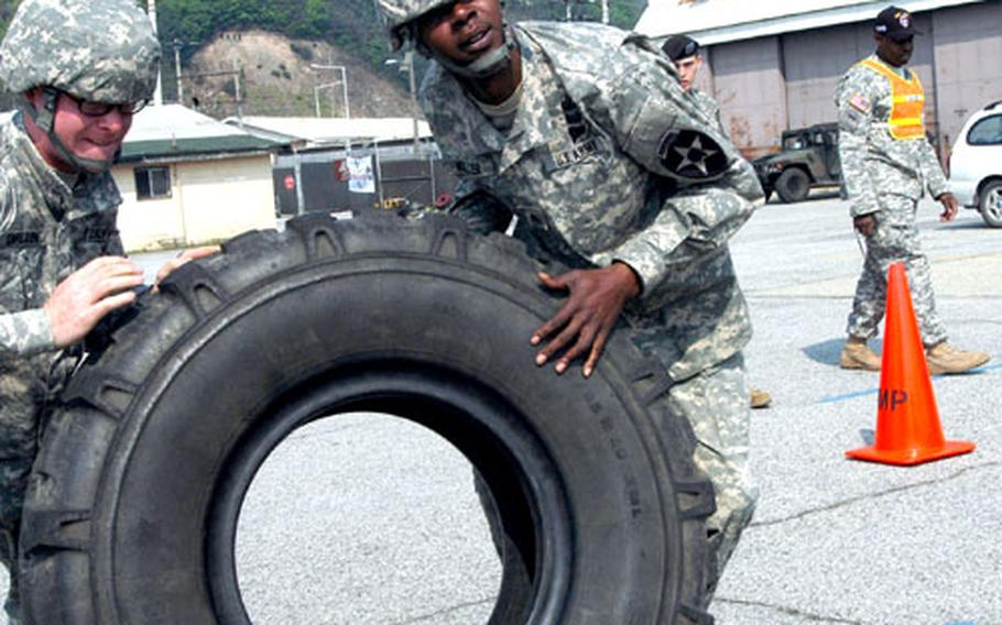 Pvt. Ian Carlson, of Milnor, N.D., and Sgt. Eric Miller of Jacksonville, Fla., flip a giant tire toward a Palletized Loading System vehicle Thursday. The tire flip and change was one of 13 events in the 302nd Brigade Support Battalion's annual Truck Rodeo.