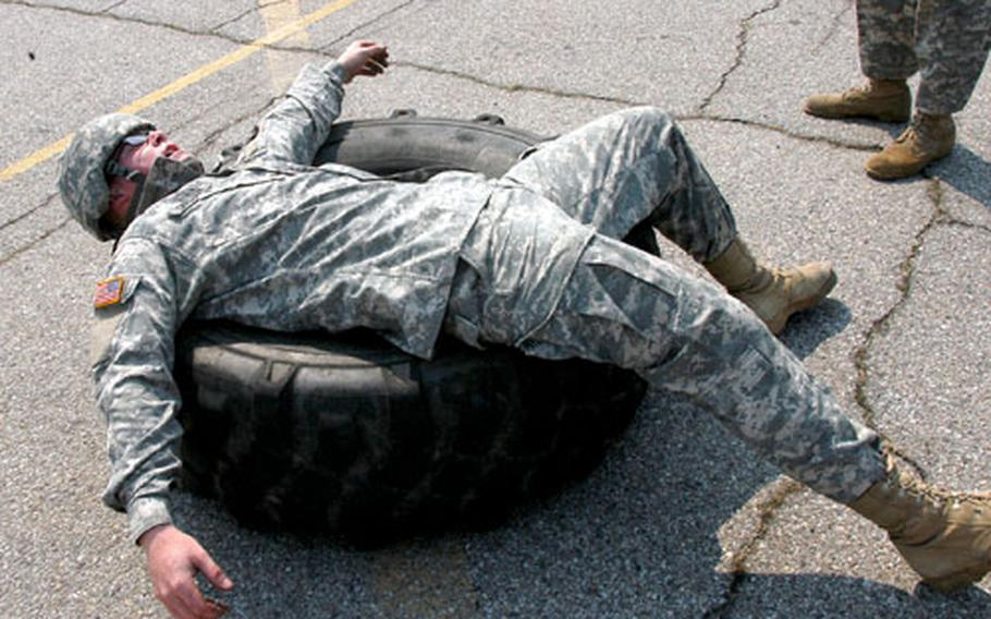 Pvt. Ian Carlson, of Milnor, N.D., takes a breather after flipping a 120-pound tire with his teammate, then changing another tire and flipping it back down a track in a timed event.