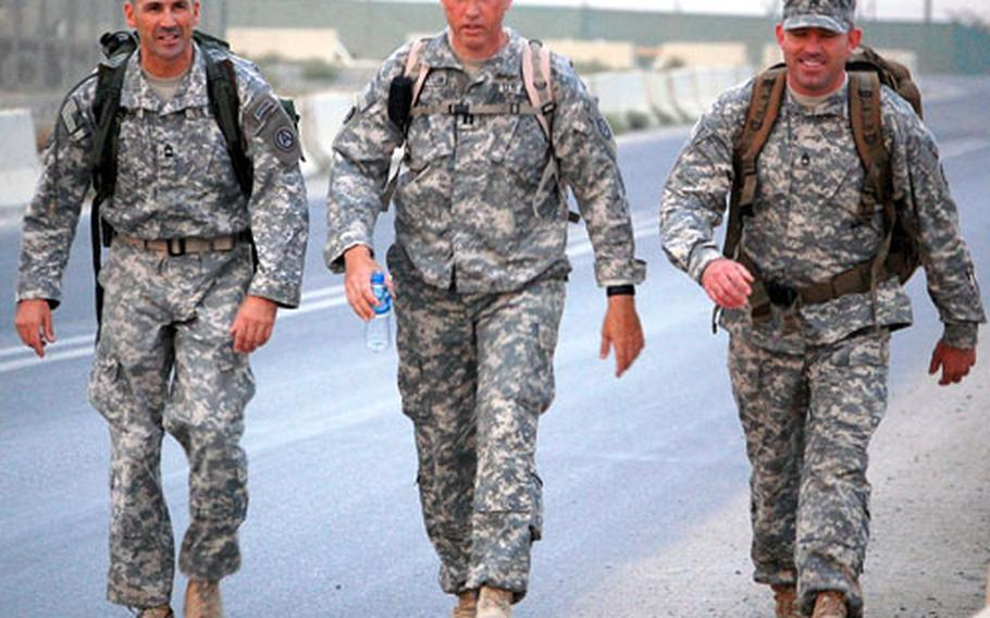 From left, Master Sgt. Charles Tennant, Capt. Robert Vandertuin and Sgt. 1st Class Derek Greenough take the heat in stride as they march in remembrance of the Bataan Death March at Camp Arifjan, Kuwait.