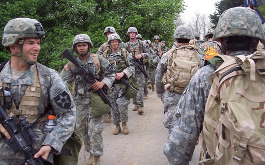 """Soldiers taking the opposite route encounter the command group around the halfway point of the 25-mile """"Manchu Mile"""" hike near Warrior Base, South Korea, on Tuesday. The event is a tradition of the 2nd Infantry Division's 2nd Battalion, 9th Infantry Regiment. It commemorates an 85-mile hike and battle by the regiment during the Chinese Boxer Rebellion in 1900."""