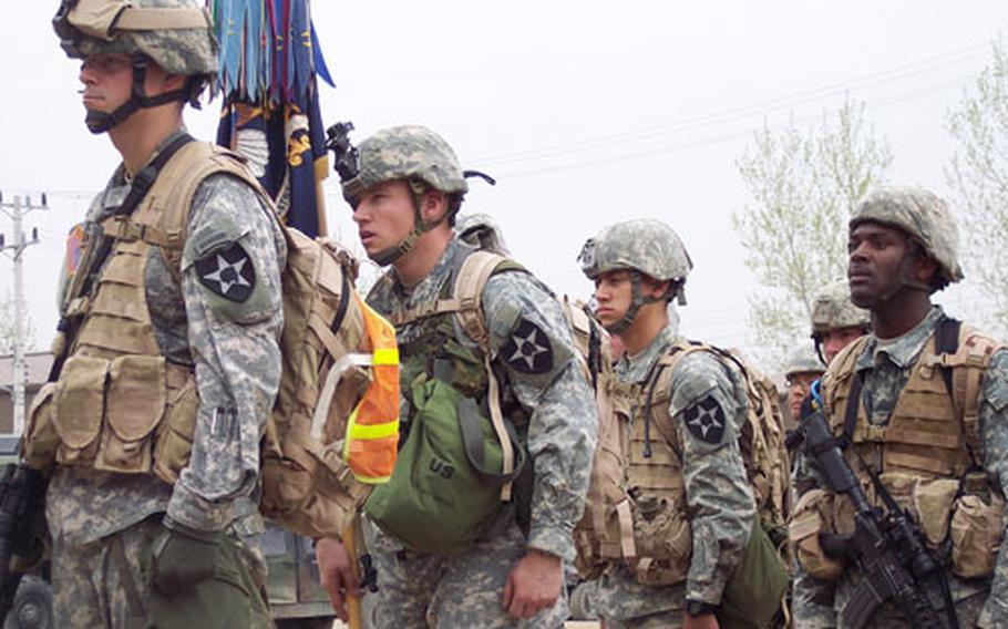 Soldiers from the lead group stand at attention as the regimental bell rings following their completion of the 25-mile Manchu Mile around Warrior Base, South Korea, on Tuesday.