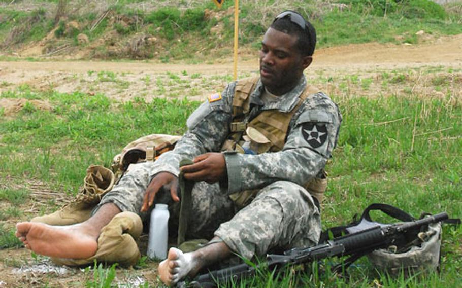 Pfc. James Roberts tends to his feet at the halfway point rest stop during the 25-mile Manchu Mile around Warrior Base, South Korea, on Tuesday.