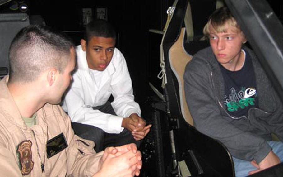 Marine Capt. Jonathan Spencer, HMM 262, left, talks about his job as a helicopter pilot with students Adrian Jimenez, 17, center, and Jonathan Parks, 16, during Job Shadow Day on Friday. The juniors from Kubasaki High School are sitting in a CH-46 helicopter simulator at Marine Corps Air Station Futenma.