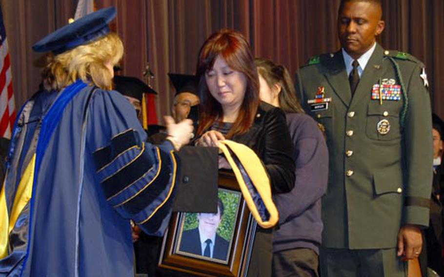 Michelle Bremer accepts a bachelor's degree diploma Saturday at Yongsan Garrison, South Korea, on behalf of her husband Chip Bremer, who died April 1. University of Maryland University College Present Susan C. Aldridge presents the diploma, joined by Maj. Gen. John W. Morgan III, 2nd Infantry Division commanding general.