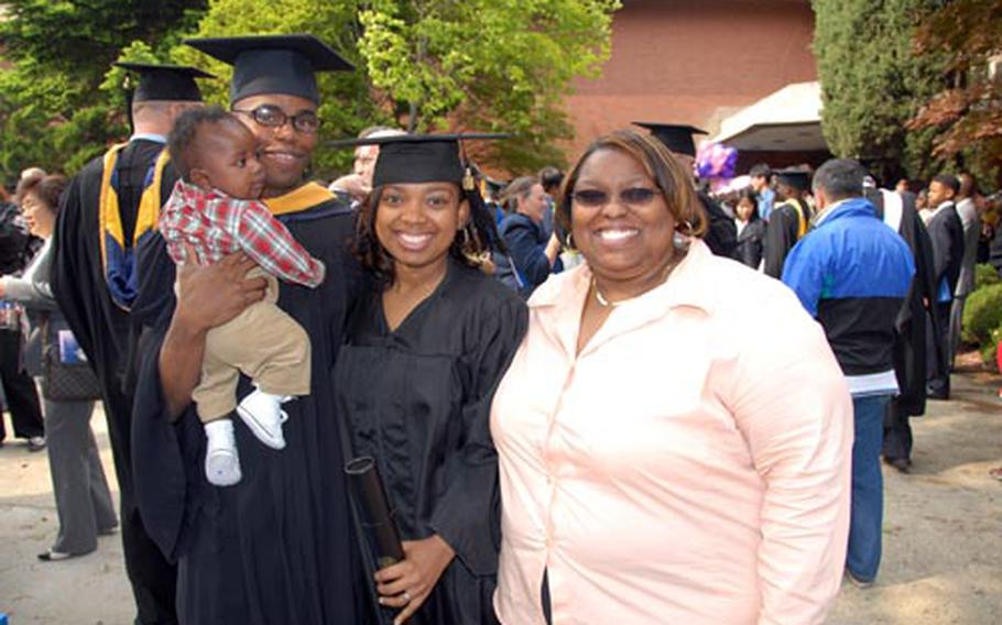 Danny and Natoya Black, their son, Danny Jr., and Natoya's mother, Cheryl McCrae, celebrate following the UMUC commencement ceremony Saturday at Yongsan Garrison, South Korea.