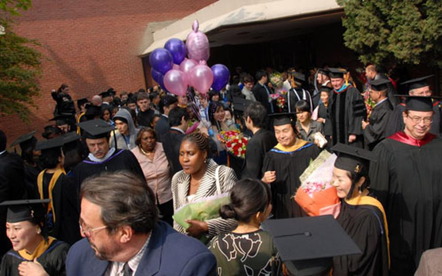 Families and friends join the graduates and faculty members following the UMUC commencement ceremony Saturday at Yongsan Garrison, South Korea.