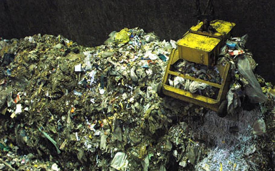 A crane lifts trash into Yokota's incinerator. The base processes 30 tons of trash every day.