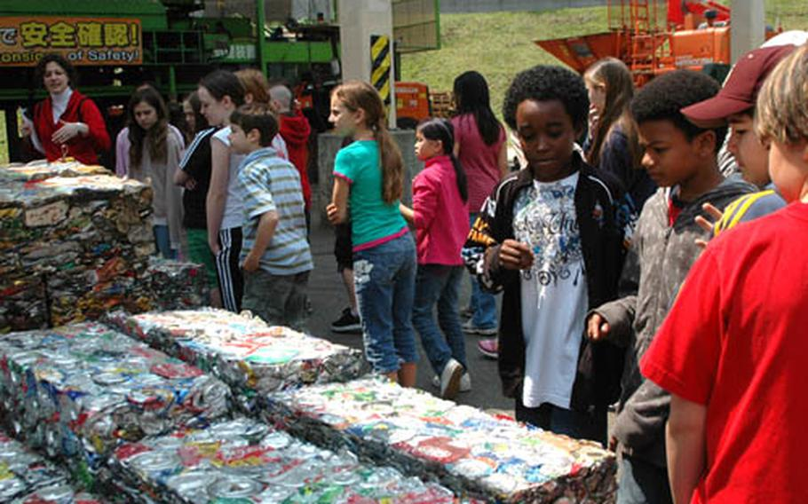 Fifth-graders from Yokota West Elementary School check out blocks of crushed cans at the base Incinerator and Processing Plant.