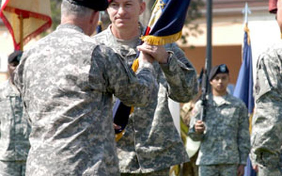 Gen. David McKiernan, U.S. Army Europe commander, gives the guidon representation the command of the Southern European Task Force (Airborne) to Brig. Gen. William B. Garrett during a ceremony in Vicenza, Italy, on Monday.