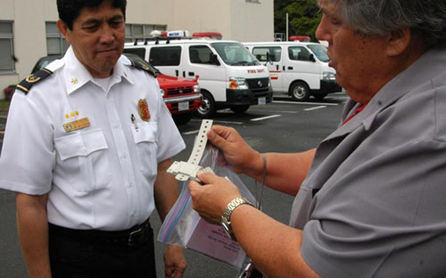 CNFJ's Fire Prevention Chief George Salcedo (left) and Charles LeFever (right) demonstrate a tie down strap that can be used to help earthquake proof a home.