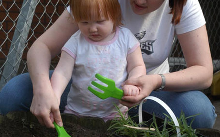 Staff Sgt. Jennifer White, with the 100th Services Squadron, helps her 1-year-old daughter, Victoria, plant flowers as part of Earth Week festivities at RAF Mildenhall's Child Development Center last week.