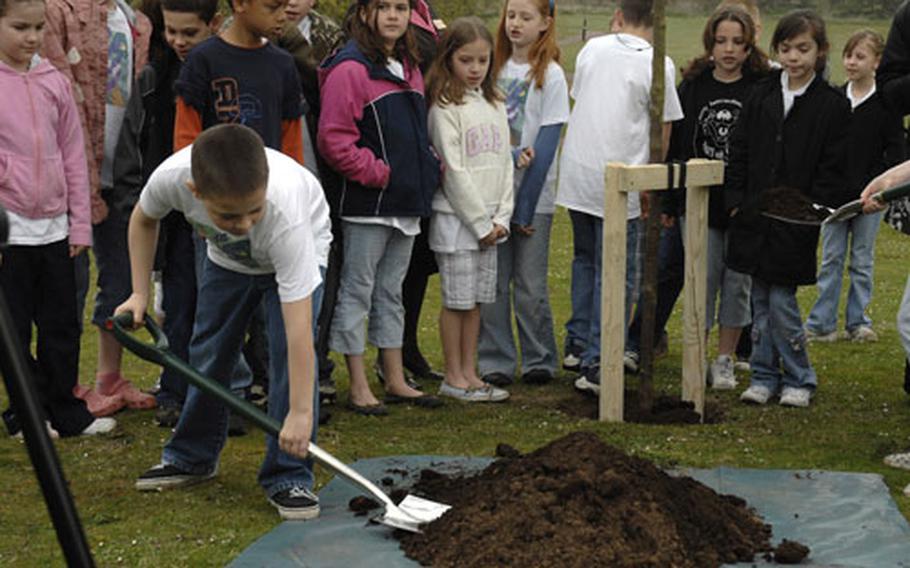 Students look on as Ryler Sturm, a member of the Lakenheath Intermediate School student council, shovels dirt to help plant a British Bird Cherry tree last week in support of Earth Week at RAF Lakenheath.