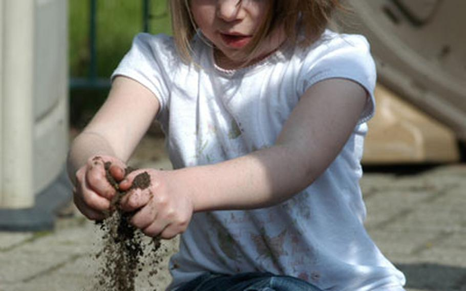 Nora Vanasse, 4, buries some seeds in a garden outside of her classroom at RAF Mildenhall's Child Development Center as part of Earth Week festivities last week.