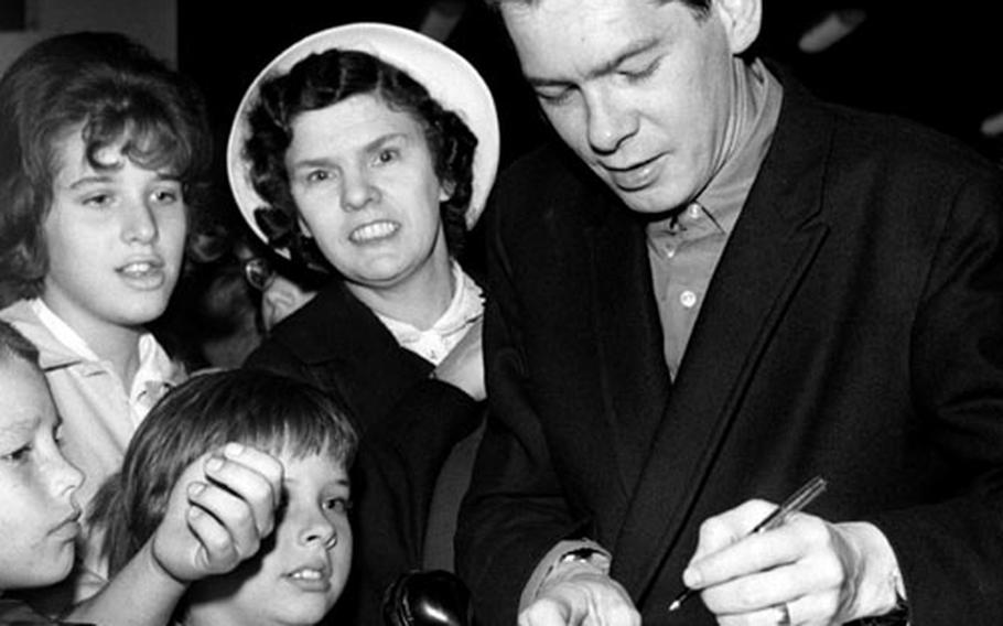 Johnnie Ray signs autographs at Wiesbaden, Germany, in 1961.