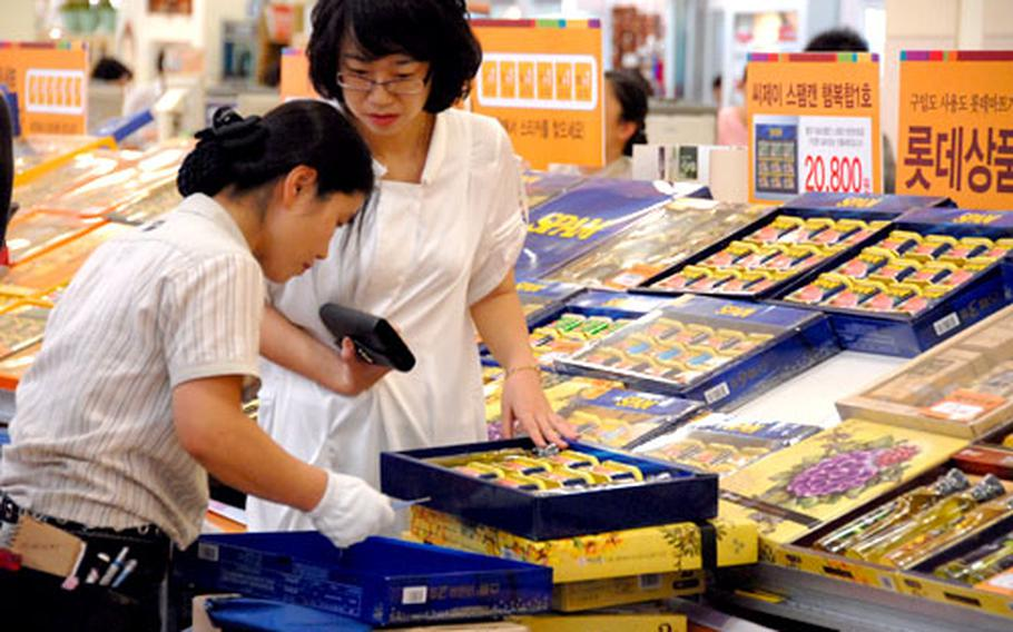A customer at Lotte Mart in Seoul Station watches as a store employee checks a gift box of Spam. South Korea is one of the world's top consumers of Spam, which is a popular gift at Chuseok, one of the country's most important holidays.