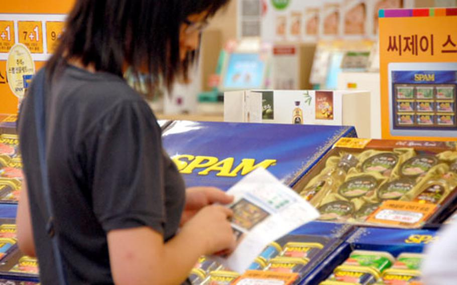 A customer at Lotte Mart at Seoul Station looks at a price list for Spam gift boxes, a popular present at Chuseok.