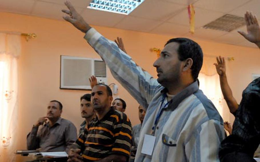"""Students raise their hands Thursday in Baghdad while attending an electricians course at Civil Service Department –Jihad. American officers started the program to help """"Sons of Iraq"""" find new jobs, but the six-month program is open to all Iraqis who want to learn new skills."""