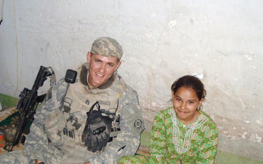 """Sgt. 1st Class Shawn Hodges, left, with Iman, the daughter of a Diyala province """"Sons of Iraq"""" leader. Hodges became close to Iman and her family during a recent deployment and, with Iman's father's permission, tried to adopt her."""