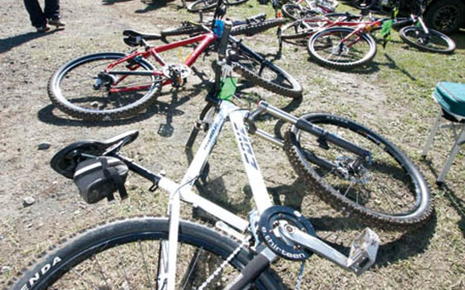 People walk past a row of bicycles Saturday at the Tour de Tama XXII Mountain Bike Race inside Tama Hills Recreation Center, Japan.