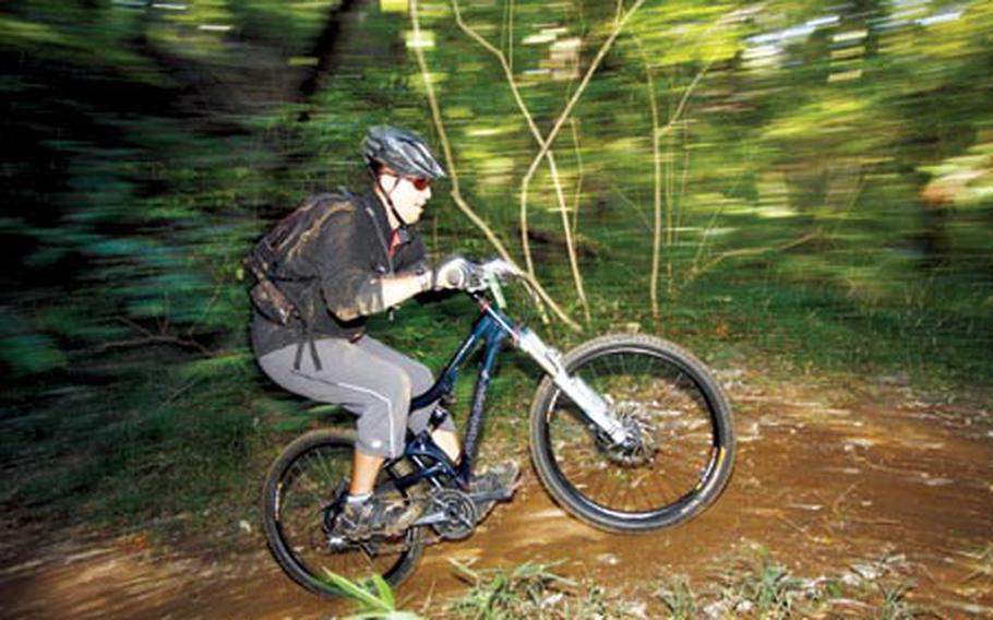 An American rider speeds along the dirt trail during Saturday's Tour de Tama XXII Mountain Bike Race at Tama Hills Recreation Center, Japan.