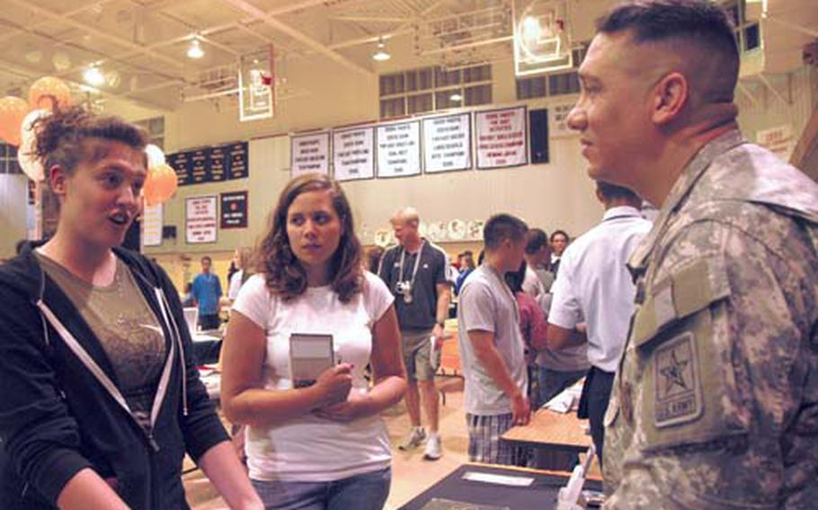 """Jasmin Barton, 18, left, and Caitlin Arnot, 17, center, speak with the Sgt. 1st Class Javier Romero, the Army recruiter on Okinawa, about options in joining the service. Both are seniors at Kubasaki High School. Barton, whose father is in the Army, said she's thinking about becoming an Army reservist to help defray college costs. Arnot said that since her family claims residency in Montana, in-state tuition costs are her determining factor for choosing a college. """"I have only one option for college, and that's Montana State University. It's an education, and it's what I can get,"""" she said."""