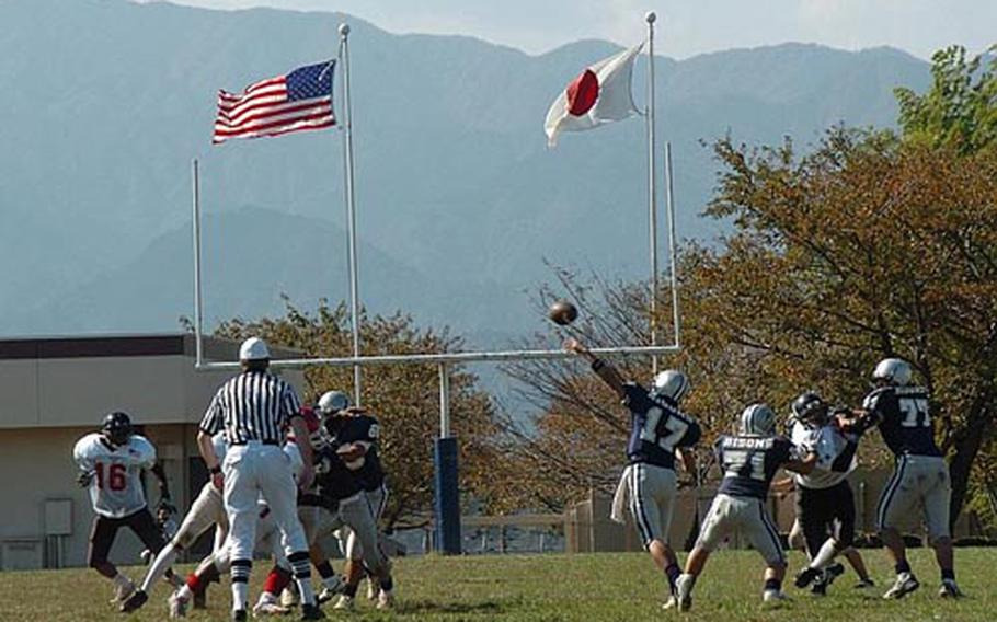 The national flags of Japan and the United States wave in the breeze Saturday, as Japanese all-star team quarterback Hiroki Nakamoto heaves the football into the end zone during the first quarter of the Tomodachi Bowl at Camp Zama. The American all stars set the tone early by returning the opening kickoff for a touchdown. They went on to win 57-20.