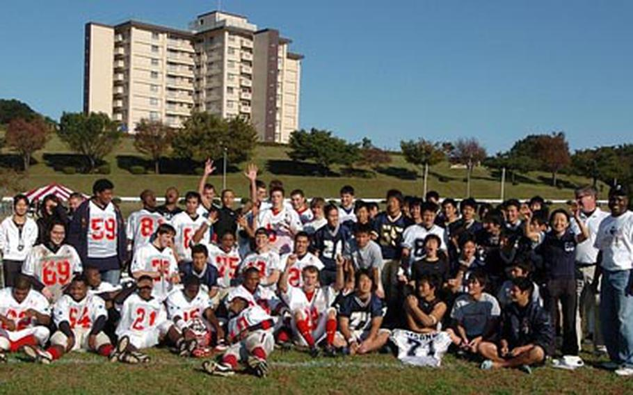 Players of the American and Japanese all-star teams get together for a group photo following the Saturday's Tomodachi Bowl at Camp Zama, Japan. The American all stars set the tone early by returning the opening kickoff for a touchdown. They went on to win 57-20.