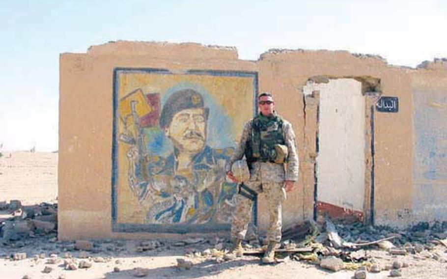 Marine Reserve Capt. Duncan D. Hunter poses next to a mural of Saddam Hussein in Fallujah in 2004. Hunter, a Republican candidate for Congress in California's 52nd District, is one of 20 Iraq and Afghanistan veterans running for national office this year.