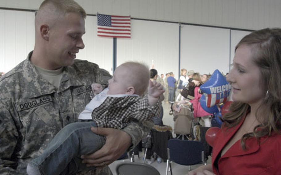 As Allison Douglass looks on, Spc. Michael Douglass holds his 6-month-old son Landen, who was born while his father was deployed to Iraq with Company C, 1st Battalion, 214th Aviation Regiment. The company returned from their 15-month deployment on Sunday.