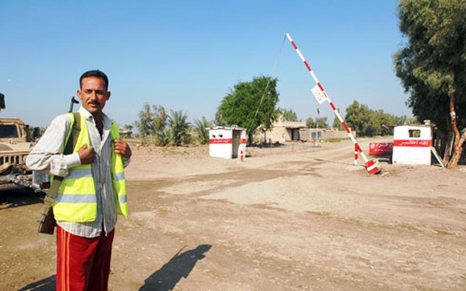 """A """"Sons of Iraq"""" member stands near a checkpoint Saturday in Radwaniyah, a district just south of Baghdad. The American unit in charge of the area started working on transferring members to Iraqi security forces about a year ago."""