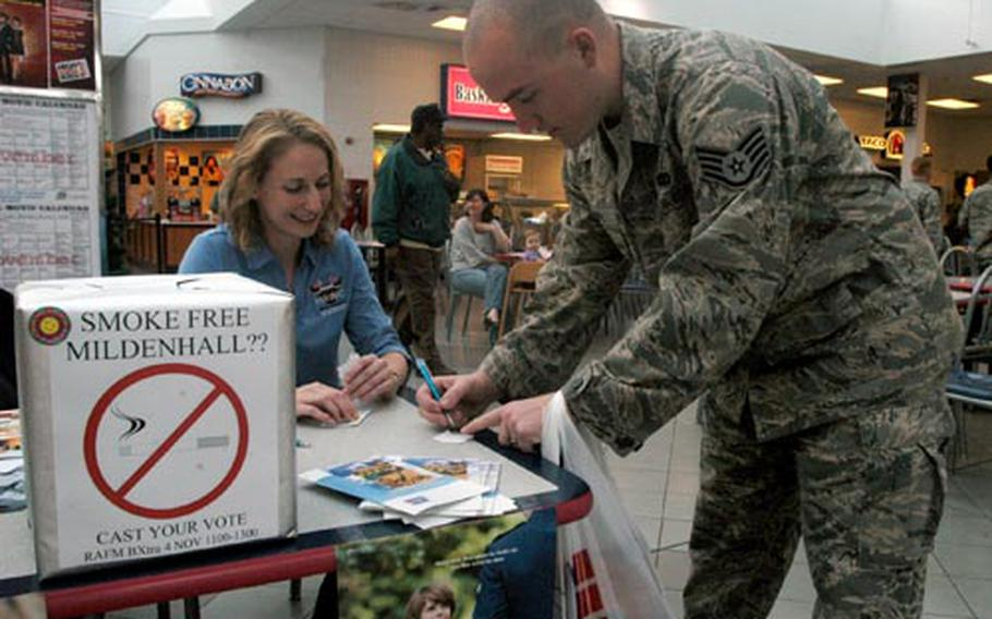 Staff Sgt. William White casts his vote in favor of a base-wide smoking ban Tuesday with Kelly Livett, information manager for the Health and Wellness Center at the base.