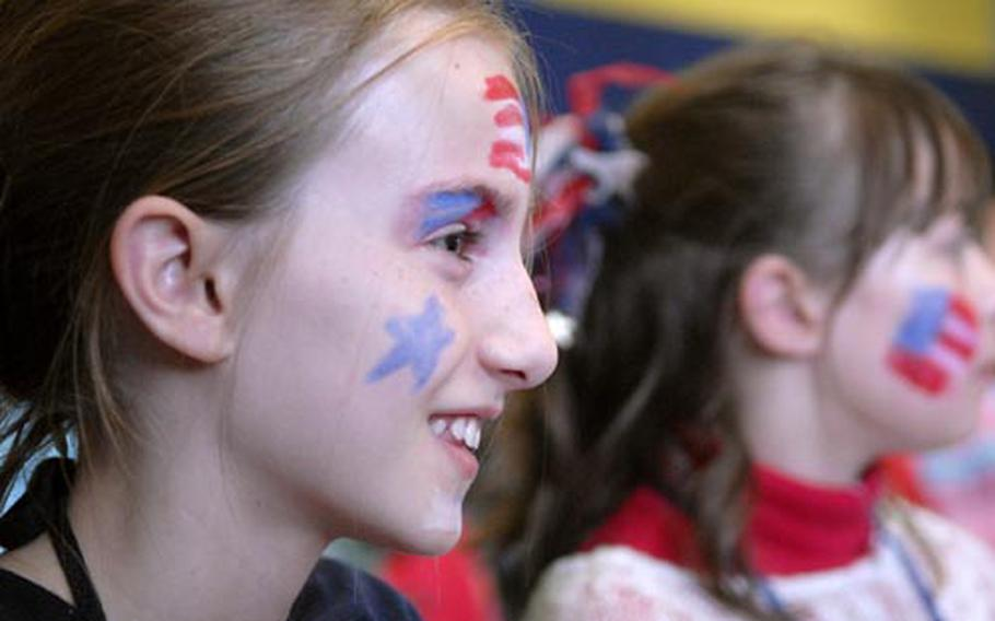 Fourth-grader Danniel Flaherty shows off her country's colors during a the mock presidential debate.