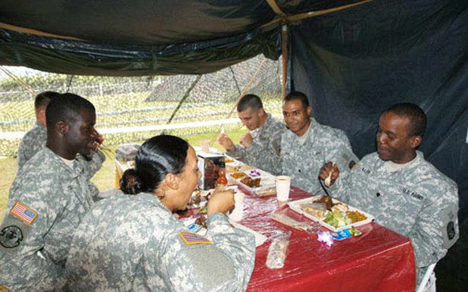 Soldiers from the 1-1 Air Defense Artillery Battalion enjoy lunch at a makeshift field dining facility at Torii Station, Okinawa, on Tuesday. Food service soldiers from the 1-1 ADA prepared and served a meal to fellow soldiers as part of an evaluation for the Philip A. Connelly food service awards.