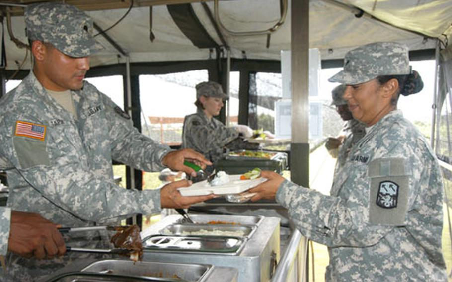 Spc. Joe Tapia, a food specialist with the 1-1 Air Defense Artillery Battalion, serves a scoop of garlic mashed potatoes Tuesday to Spc. Dawn Lee at Torii Station, Okinawa