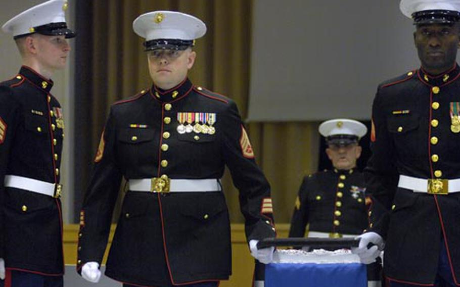 Staff Sgt. Ben Coleman, left, and Sgt. Recordo Demetrius march the Marine Corps cake down the aisle at the conclusion of a ceremony commemorating the 233rd birthday for the Corps Friday at Landstuhl.