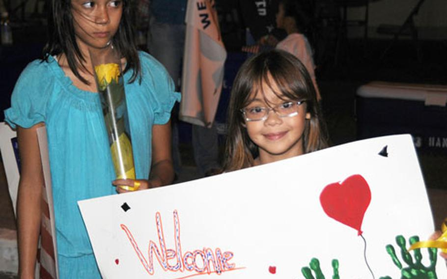 Hannah, left, 13, and Sarah Parkhurst, 9, planned to give their father, Gunnery Sgt. Timothy Parkhurst, yellow roses as they welcomed him home to Camp Schwab on Thursday evening after his seven months in Iraq.