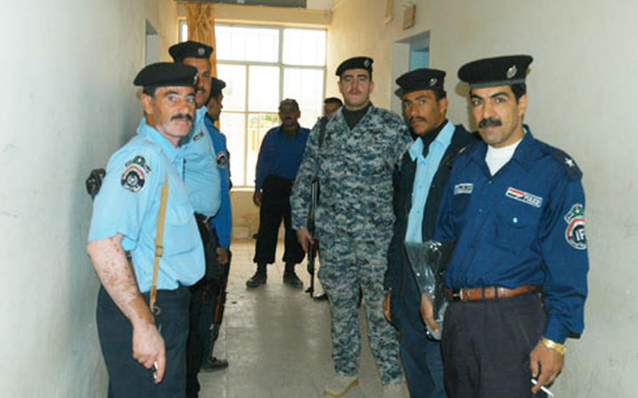 Police at the Haditha police station wait in line for paychecks Thursday.