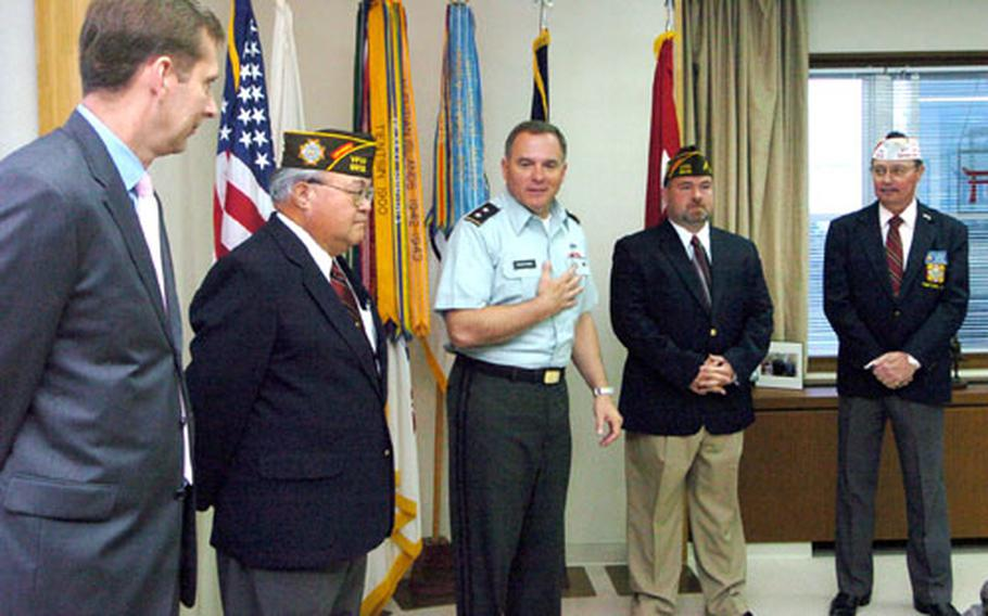 Camp Zama's cammander, Major Gen. Francis J. Wiercinski, center, expresses his appreciation to members of VFW 9612 before presenting them with a national award for community service Friday.