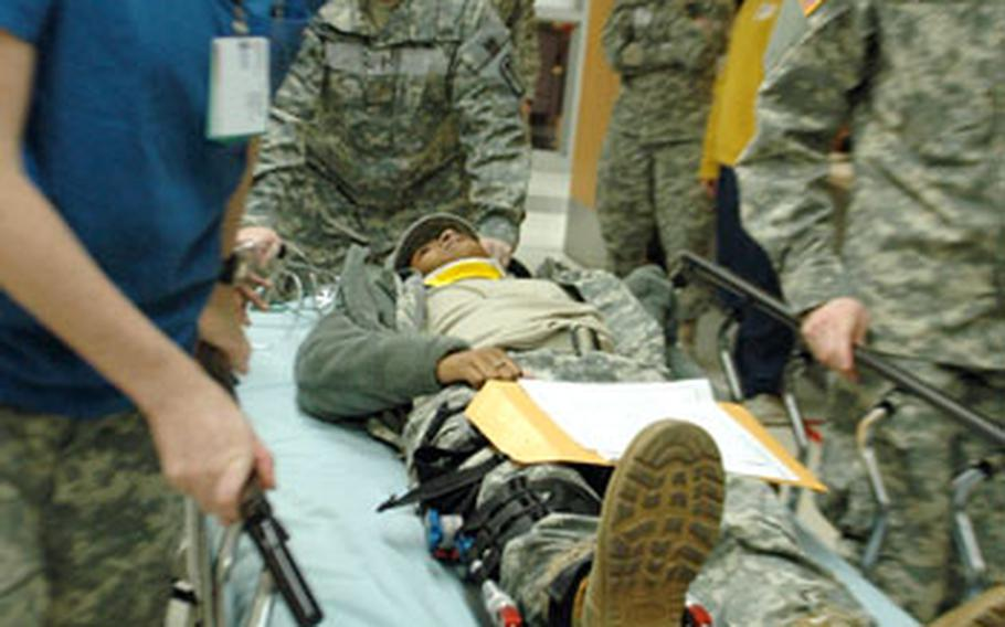 """Pfc. Megan Downey, left, shouts """"Make a hole!"""" as she and other Brian Allgood Army Community Hospital emergency room staff rush a mock patient up to the intensive care unit Thursday."""