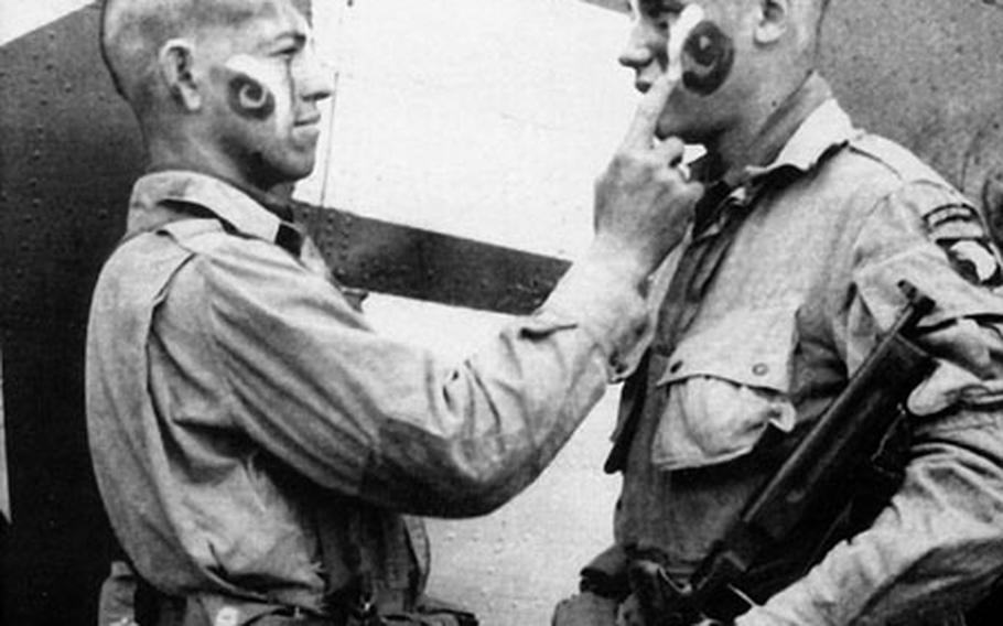 """This photo of paratroopers Clarence C. Ware and Charles R. Plaudo painting each other's faces on the afternoon of June 5, 1944, was printed in Stars and Stripes, and helped form the legend of """"The Filthy Thirteen."""""""