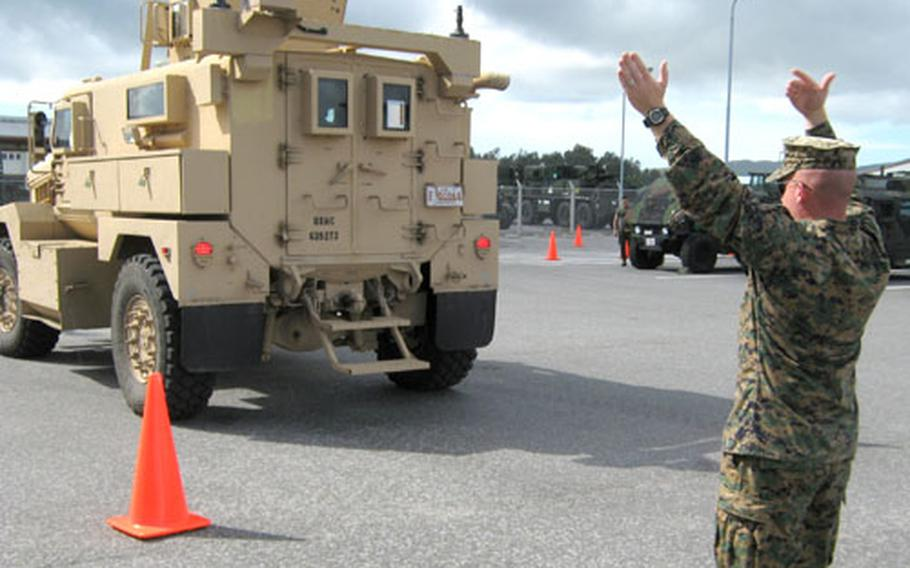 Sgt. Daniel J. Fisher, 25, of Milwaukee, the primary instructor for the MRAP course, acts as a ground guidefor a student backing up at Camp Hansen on Thursday.