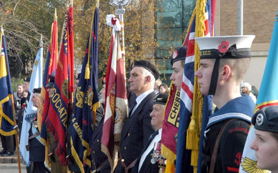 Britons young and old bearing the colors of their military organizations listen during a Remembrance Day ceremony in Cambridge.
