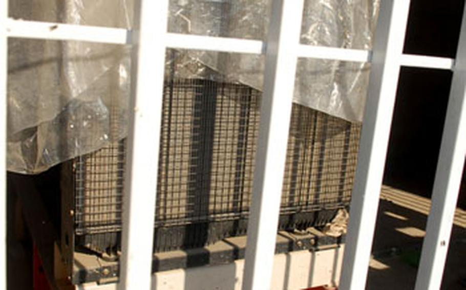 """A new generator sits securely behind locked bars in Baghdad's al-Iskan neighborhood. American units are training Iraqis, many of whom are """"Sons of Iraq"""" members, on how to maintain the generators so that the equipment can function without continued American help."""