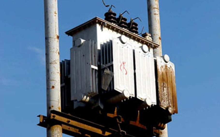 A four-month-old transformer sits idle on a rusty power pole in Baghdad's al-Iskan neighborhood. Workers have yet to connect it to the power grid.