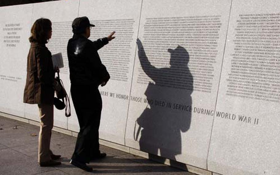 Lynn Bettancourt helps her father, Grant Hirabayashi, find his cousin's name at the Japanese American Memorial to Patriotism during World War II.