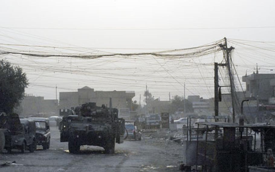A Stryker from the 1st Battalion, 27th Infantry Division passes under power lines in Istiqual, Iraq, near Sadr City, in September. U.S. forces here have complained to locals about the makeshift lines and the danger they pose. U.S. commanders say locals split and reroute power lines to provide electricity to their homes.