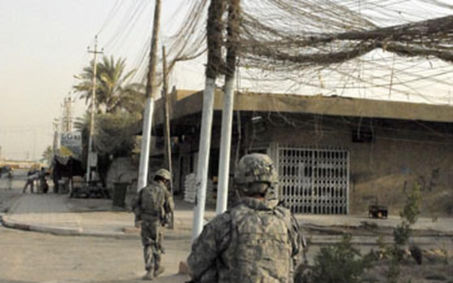 Troops from Company A, 2nd Brigade, 4th Infantry Division patrol a street in the Doura neighborhood of Baghdad in August, below a tangle of power lines.