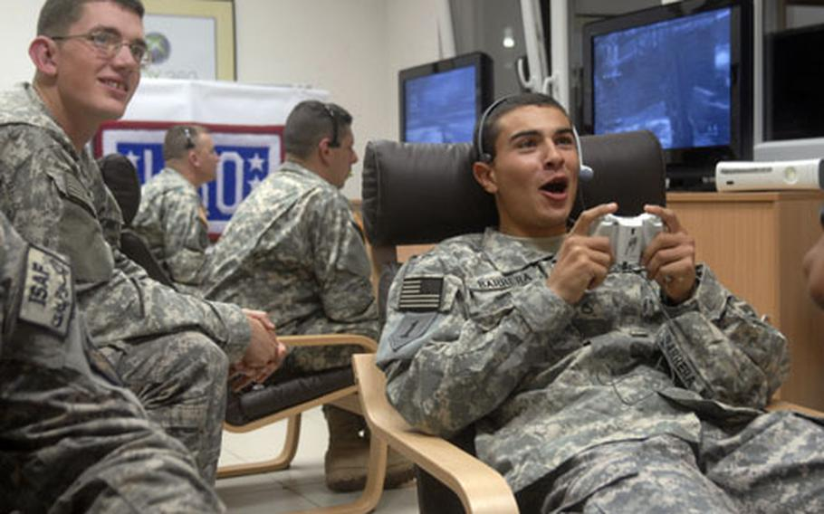 """Pfc. Reimaldo Barrera, right, plays """"Call of Duty 5"""" against players with the NFL's Tampa Bay Buccaneers and fellow troops stationed around the world as part of a USO/Pros vs. GI Joe gaming competition on Veterans Day. The soldiers are outpatients at Landstuhl Regional Medical Center and were playing at the newly opened USO Warrior Center on Landstuhl."""