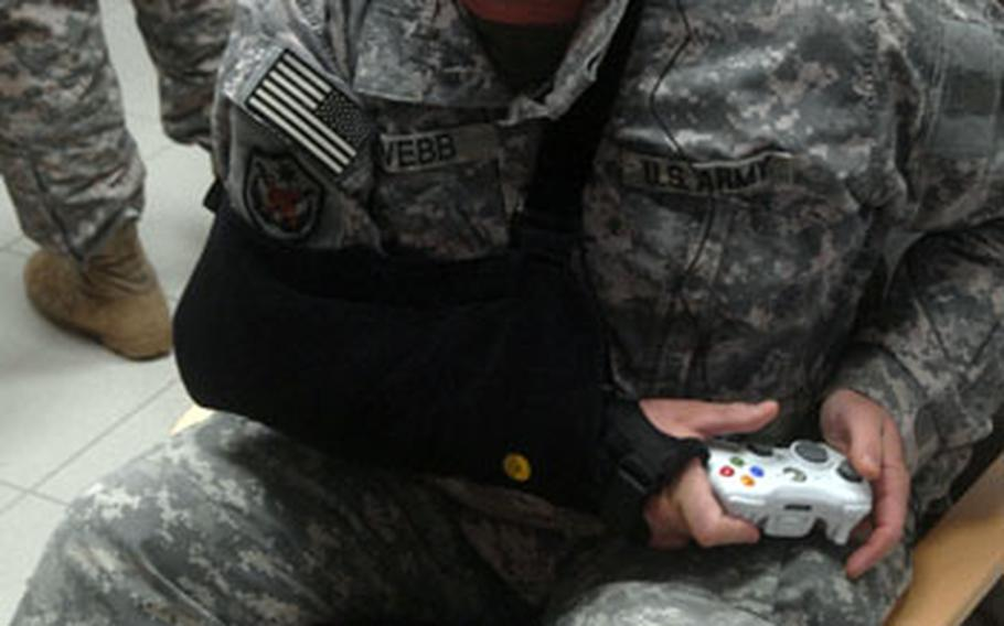 """Not hampered by a shoulder sling, Sgt. Steve Webb plays """"Call of Duty 4."""""""